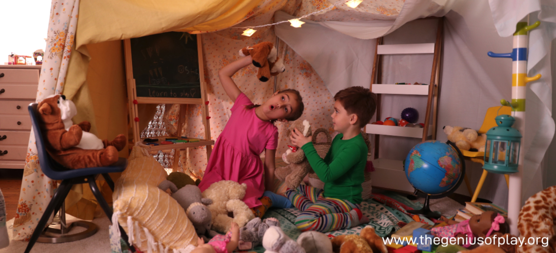 Girl and boy playing in indoor bedroom fort