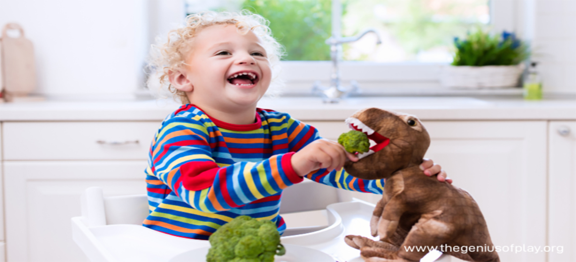 Young child feeding broccoli to a toy dinosaur