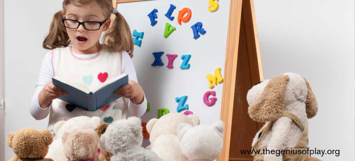 young girl playing teacher with magnetic letters and stuffed animals