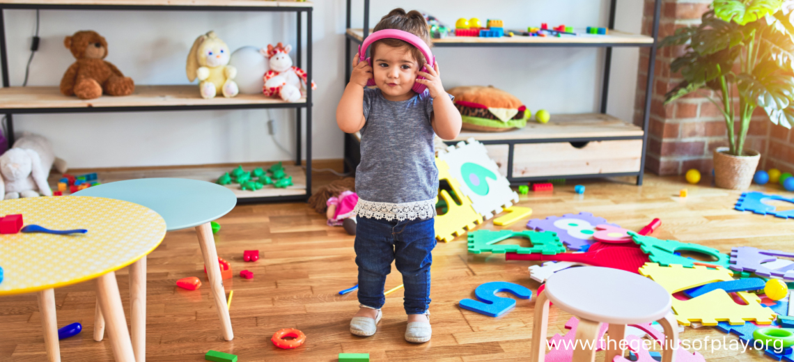 young child wearing headphones in cluttered toy room