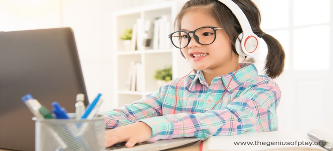 Elementary school age girl wearing headphones typing on computer