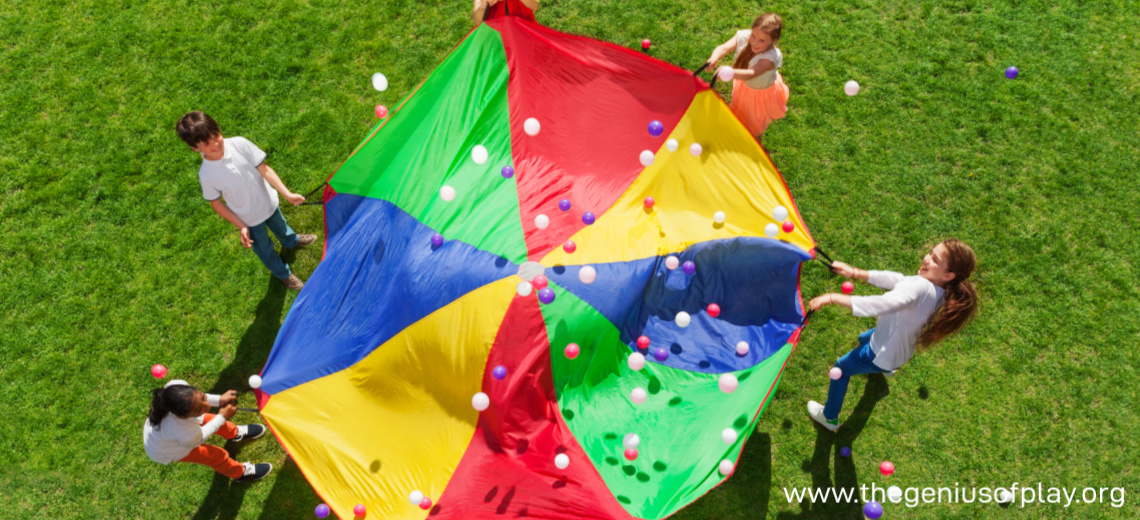young children waving a large colorful parachute up in the air outdoors