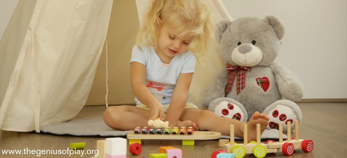 toddler girl playing xylophone with stuffed animal by her side