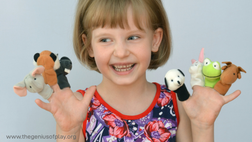 young child playing with finger puppets