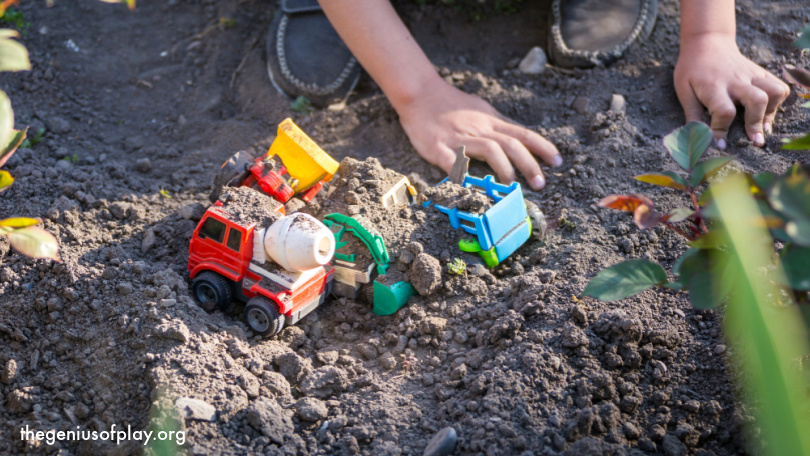 young children's hands playing with toy trucks in dirt