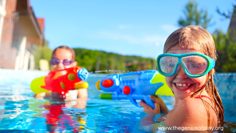 two elementary school age girls playing with water blasters in a swimming pool